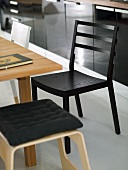 Black kitchen chair and bright wooden stool with pad