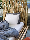 Matress and plaid bed linen on a frame of laminated wood in front of a screen made of natural wood branches