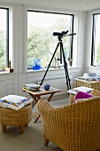 Rattan chair and foot stool around a wooden side table next to a tripod with camera in front of a bank of windows