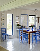 Open plan design dining room with white wood paneling and blue chairs at the dining table in front of a patio door