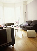 A modern lilac sitting room with upholstered sofa, armchair, white coffee table, wood floor