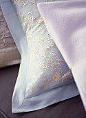 A detail showing delicately embroidered cushion