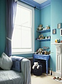 A detail of a child's blue bedroom with a painted table, shelves, gingham curtains, soft toys, covered sofa