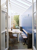 Looking through an open door in to a modern, country conservatory with stone floor, table and bench seat