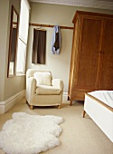 A detail of a neutral traditional bedroom with a free standing wardrobe, upholstered armchair, furry rug