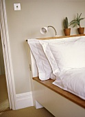 A detail of a modern bedroom with a platform bed, white bed linen