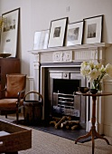 A detail of a traditional sitting room, showing carved fireplace with black hearth, wooden round side table