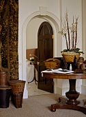 A traditional hallway with an arched doorway, door open, wooden round pedestal table, wicker baskets