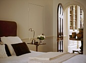 A detail of a traditional bedroom, bed with upholstered headboard, bedside table, lamp, arched doorway, door open
