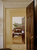 A traditional hallway with a pair of doorways, panelled doors open, ornate plaster work cornices, view into sitting room