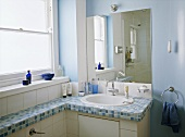 A detail of a modern blue bathroom with a washbasin set in a unit with mosaic tiled top, mirror