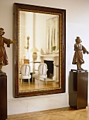 Statues on plinths either side of mirror reflecting sitting room