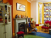Green cupboard next to fireplace in yellow sitting room