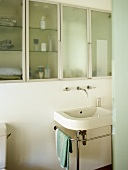 Bathroom with washbasin on chrome stand and glass fronted cupboards.