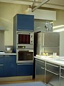 Offene Küche mit blauen Schrankfronten und Edelstahlfronten