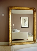 Large gold painted framed mirror against brown wall reflecting bed