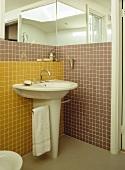 Badezimmerecke mit freistehendem Waschbecken vor gelben und braunen Mosaikfliesen