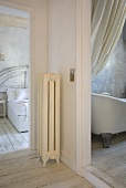 A view from an anteroom through an open doors into a bathroom and a bedroom