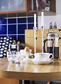 A detail of a modern kitchen, wood breakfast table, cup and saucer, coffee, caffetiere, boiled egg, candlesticks, candles,
