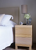 A detail of a modern bedroom, double bed with upholstered headboard, lamp, bedside table, flowers, vase, clock,