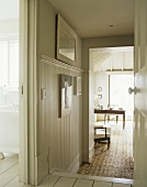 A country hallway, painted floorboards, view through open door to home office study room, wall panelling,