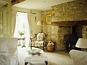 Living room fireplace with an exposed stone wall.