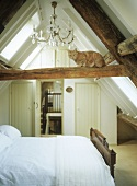 Beamed attic bedroom with a cat sitting on a beam.