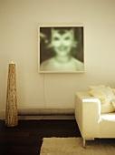 Upholstered cream sofa beneath artwork