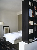 A single bed behind a partition of book shelves