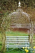 Wooden bench seat under an ornate wrought iron canopy with climbing plants