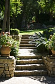 Potted plants next to stone steps leading up to lawn