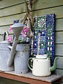 Enamel teapot and watering can on wooden table
