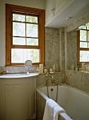 Sink set in cupboard unit next to bathtub