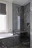 Badewanne neben Duschbereich mit offener Glastür und grauer Steinverkleidung an Wand und Boden