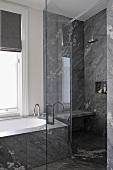 Shower unit with glass door next to bathtub below window with grey roman blind in contemporary bathroom