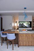 Blue bar stools at island unit breakfast bar with wooden drawers in contemporary kitchen