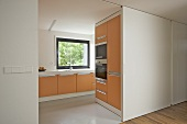 Modern kitchen with orange units and a open white sliding door