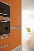 Orangefarbene Fronten am Einbauschrank mit Einbaugeräten in moderner offener Küche