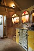 Küchenzeile und beleuchtete Wandnischen in rustikaler Küche