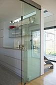 Offene Glasschiebetür mit Blick in moderne Küche