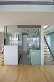 View through glass screen to modern galley kitchen