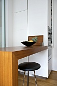 Bar stool at breakfast bar in modern kitchen