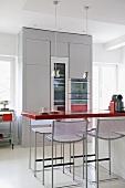 Barhocker und Theke mit roter Platte in moderner Küche