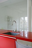 Chrome tap fitting over sink in modern kitchen