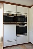 Moderne Küche mit weißen Schrankeinheiten und integrierten Einbaugeräten