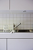 Chrome tap above kitchen sink set in white fitted units