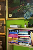Collection of portrait paintings above book shelf