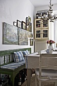 Country style dining room with green bench and wooden table