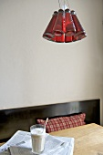 Red ceiling light above wooden table