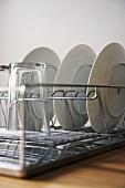 weiße Teller im Geschirrtrockner aus Metall